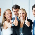 Business approval - Portrait of confident young colleagues with thumbs up sign